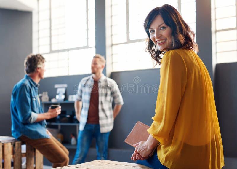 年轻女实业家坐有同事的一张书桌在背景中 免版税库存照片