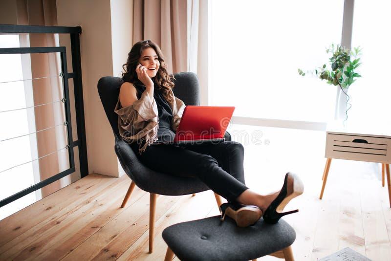 年轻女实业家工作在家 坐在椅子和握腿的繁忙的模型在小凳子 谈话在电话 ?? 免版税库存图片