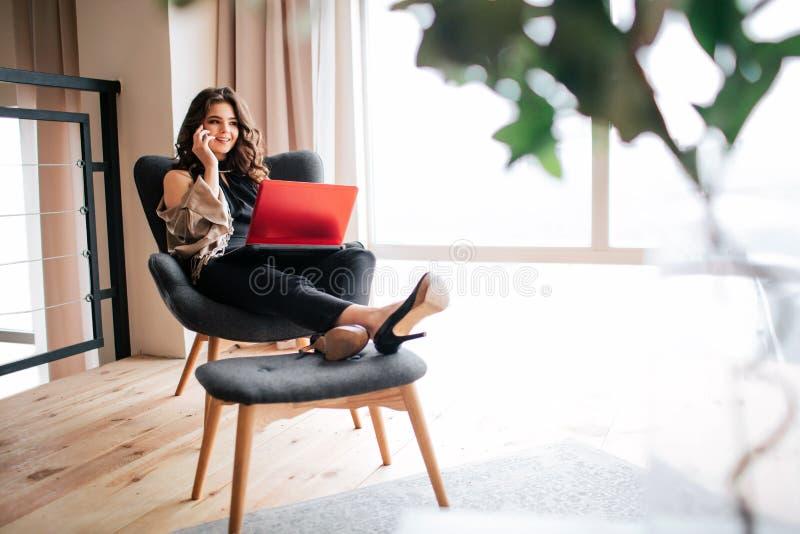 年轻女实业家工作在家 美好的快乐的模型谈话在电话和微笑 r 拿着膝上型计算机  免版税库存照片