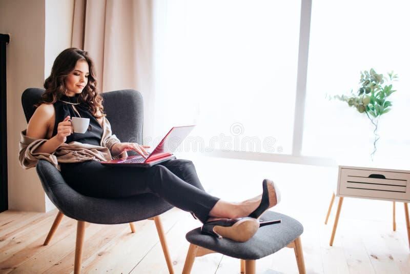 年轻女实业家工作在家 饮用的coffe和学习 握在小凳子的脚 键入在键盘膝上型计算机 免版税库存图片