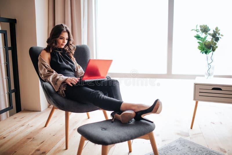 年轻女实业家工作在家 r 坐椅子和键入在膝上型计算机的键盘 单独在客厅 库存图片