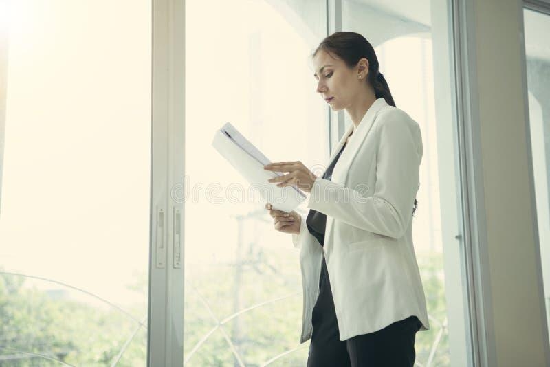 年轻女实业家待办卷宗文件在办公室 免版税库存图片