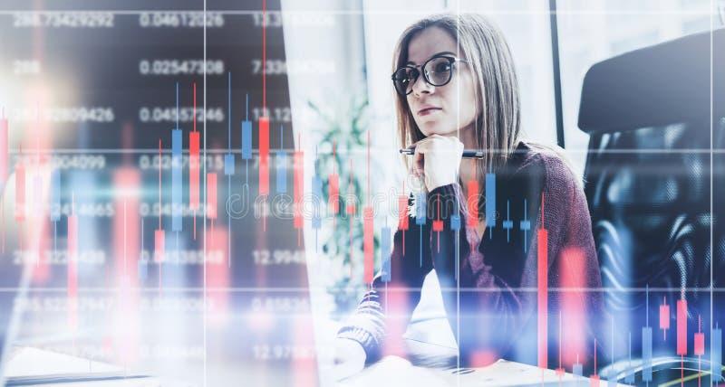 年轻女实业家有财政图表和统计的前面手提电脑坐显示器 r ? 库存图片