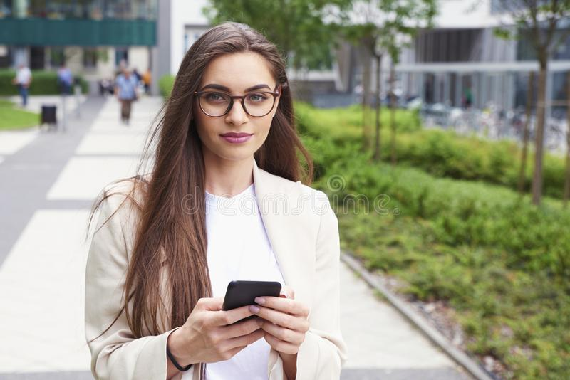 年轻女实业家正文消息,当走在街道上在城市时 免版税库存图片