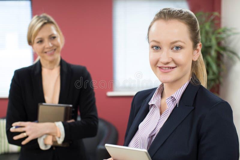 年轻女实业家画象有女性辅导者的在办公室 库存照片
