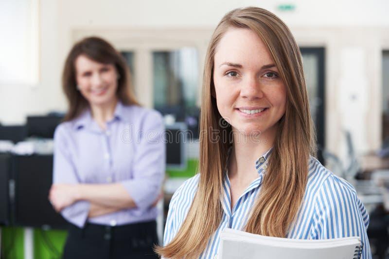 年轻女实业家画象有辅导者的在办公室 库存照片