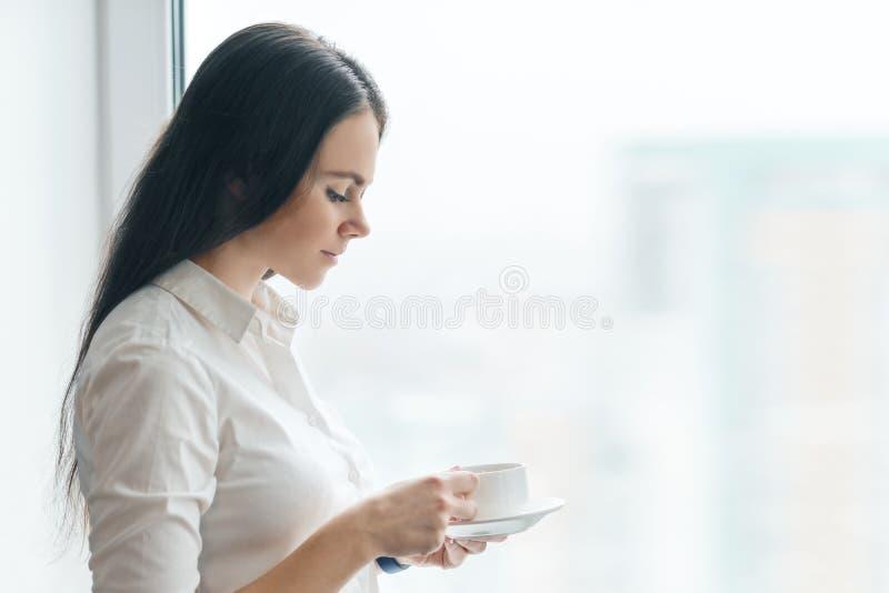 年轻女实业家画象白色衬衫的有咖啡的,享用她的早晨芳香咖啡,办公室的微笑的妇女  库存图片