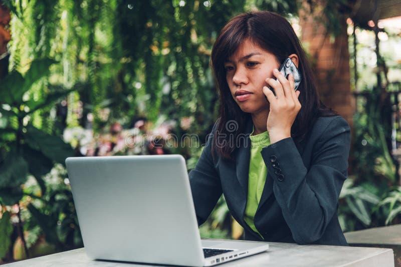 年轻女实业家谈话在有他的流动巧妙的电话clien 免版税图库摄影