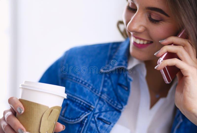 年轻女实业家谈话在电话在咖啡馆 库存图片