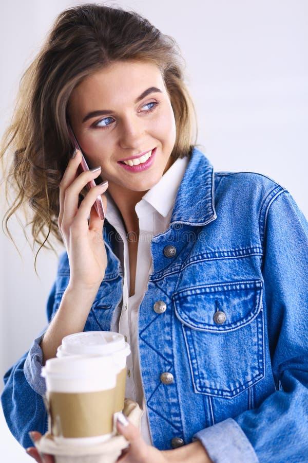 年轻女实业家谈话在电话在咖啡馆 免版税库存照片