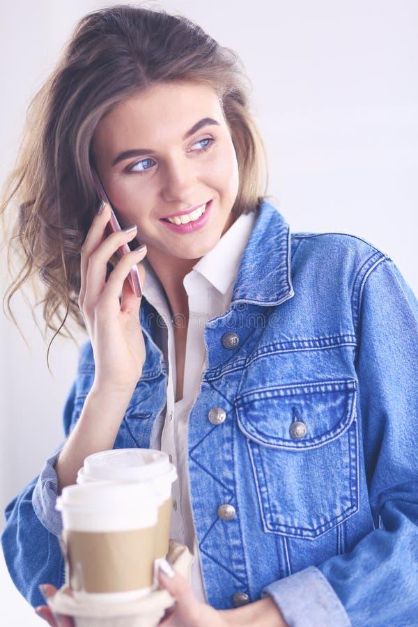年轻女实业家谈话在电话在咖啡馆 免版税库存图片