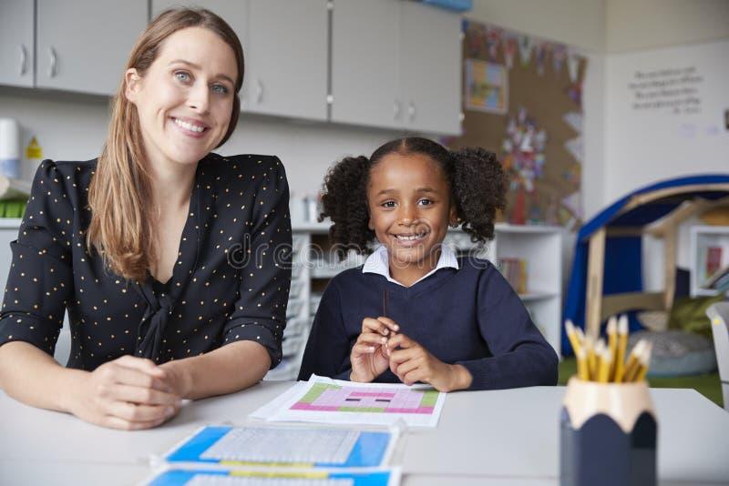 年轻女性主要学校老师和女小学生在桌上,运作一坐一个在教室,微笑对照相机,前面 库存图片
