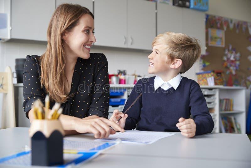 年轻女性主要学校老师和男小学生在运作一的桌上坐一个,看彼此微笑,正面图 免版税图库摄影
