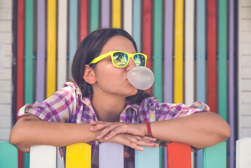 年轻女性倾斜在篱芭和口香糖 免版税库存图片