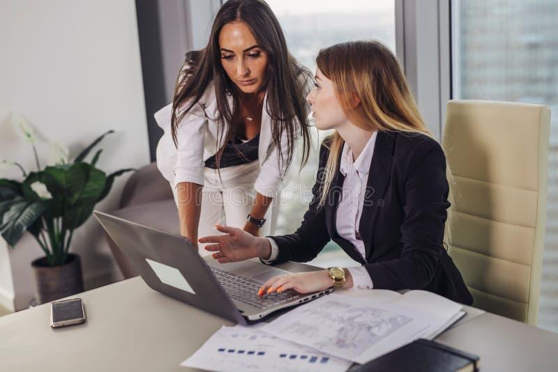 年轻女性助理与一个总经理协商显示在膝上型计算机屏幕上的数据和请求坐在的忠告 免版税库存图片
