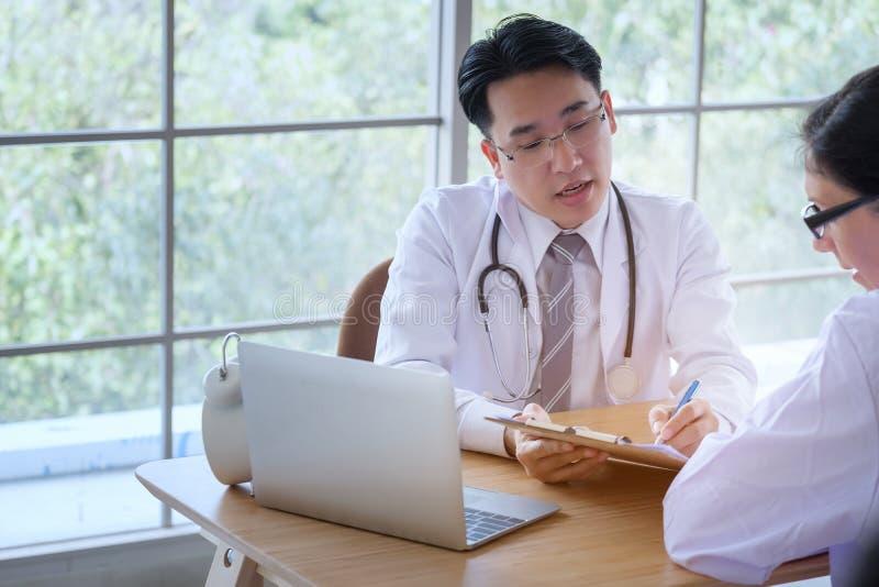 年轻女性医生咨询坐在医生办公室的患者 d 免版税图库摄影