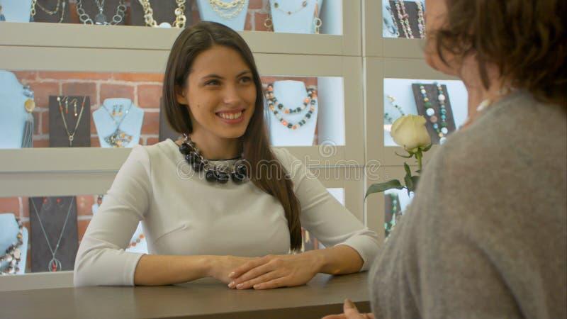 年轻女性卖主见面并且听来到首饰店的买家 免版税图库摄影