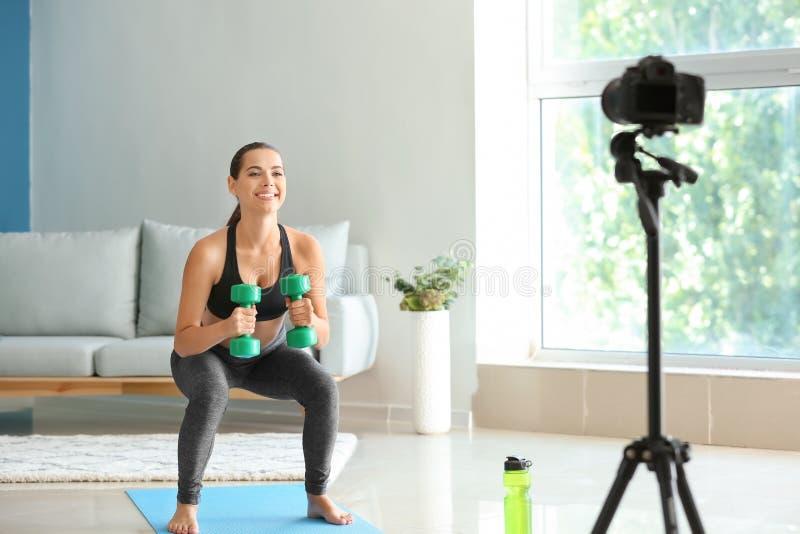 年轻女性博客作者记录的体育录影在家 免版税库存照片