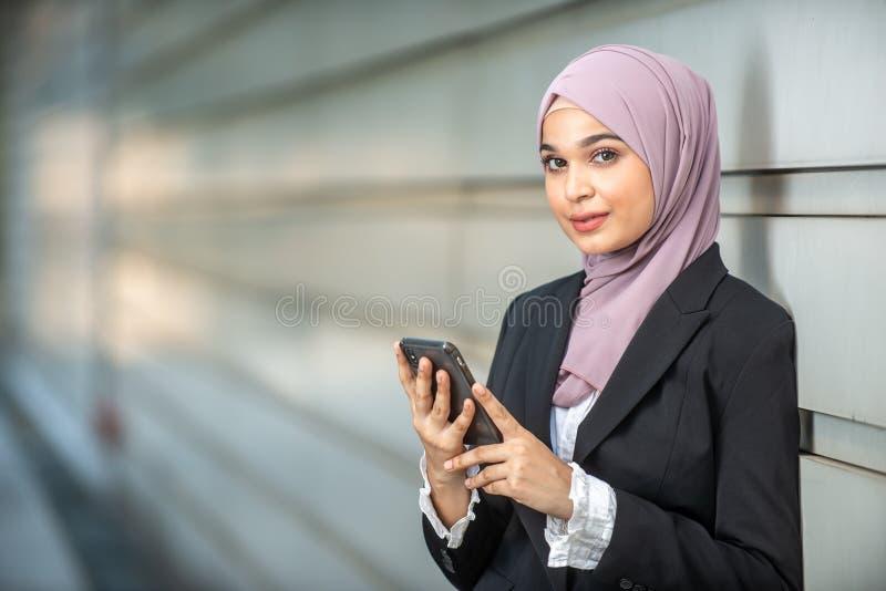 年轻女性回教企业家和她的智能手机 库存图片