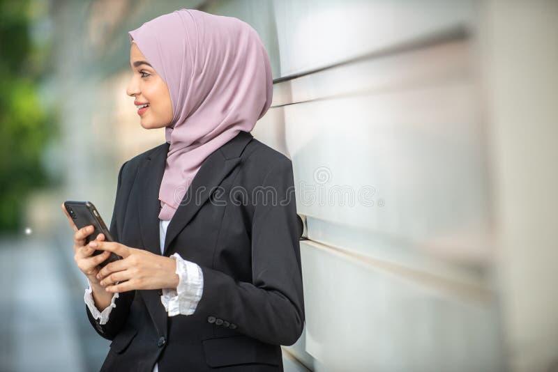 年轻女性回教企业家和她的智能手机 免版税库存照片