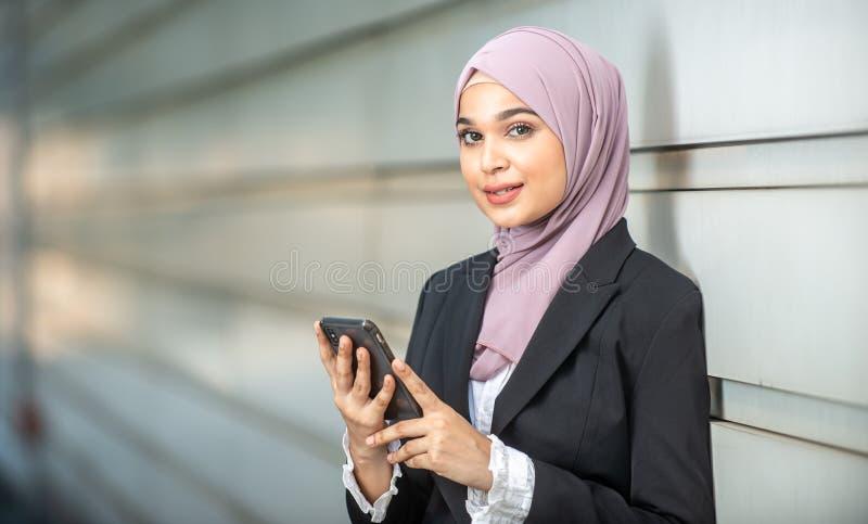 年轻女性回教企业家和她的智能手机 库存照片