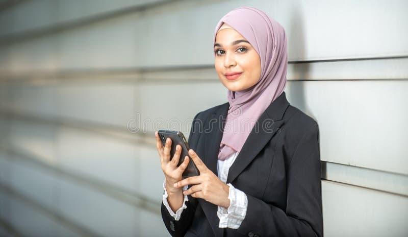 年轻女性回教企业家和她的智能手机 免版税图库摄影