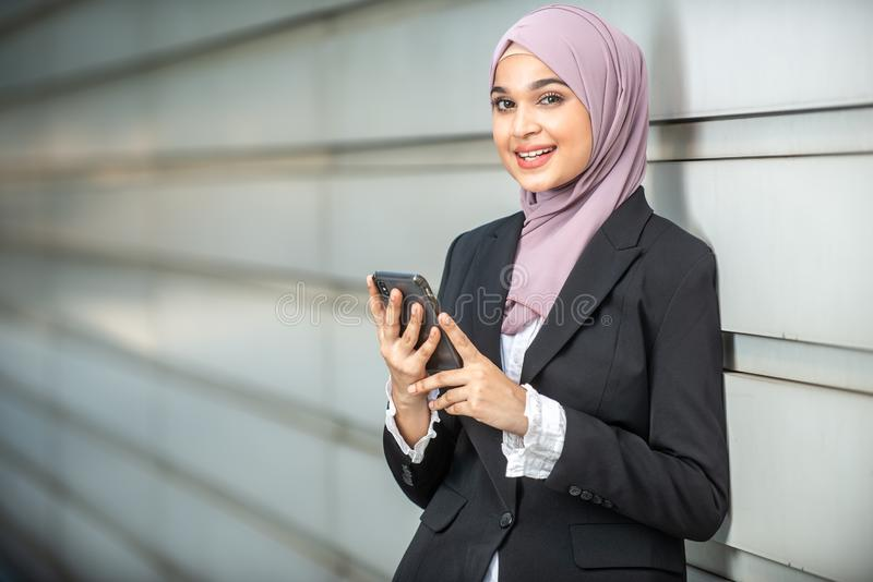 年轻女性回教企业家微笑,拿着她的智能手机 库存照片