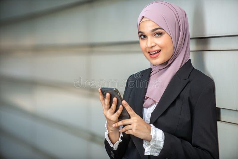 年轻女性回教企业家微笑,拿着她的智能手机 图库摄影