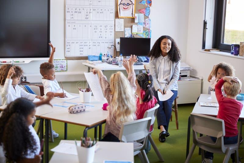 年轻女性婴儿学校老师坐面对学校孩子的椅子在教室,举他们的手回答问题 库存照片