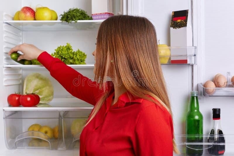 年轻女性室内射击有长期平直的黑发的,在冰箱上架子把菜放,吃仅健康食物 妇女 图库摄影