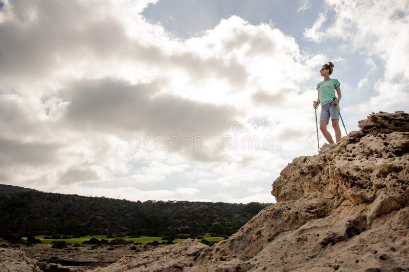 年轻女性徒步旅行者立场用在石头的棍子 图库摄影