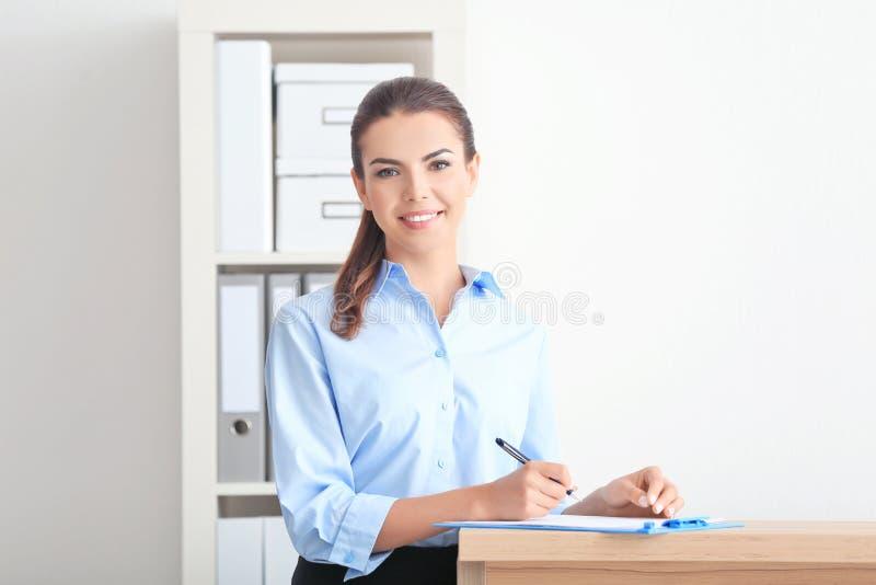 年轻女性接待员在运作的办公室 免版税库存图片