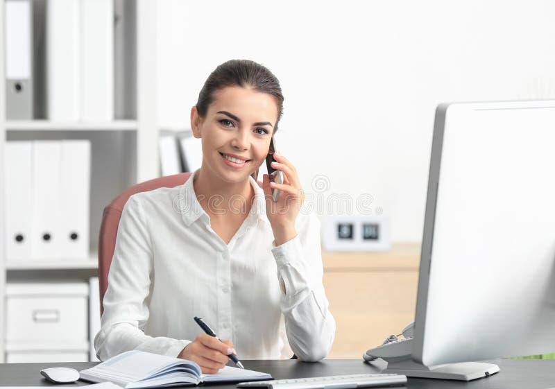 年轻女性接待员谈话在电话 免版税库存照片