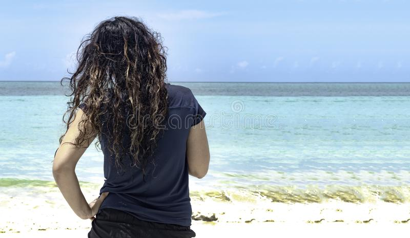 年轻女性救生员,有美丽的卷发的观察游泳者安全,绿松石水风平浪静,用在臀部的手 免版税库存照片