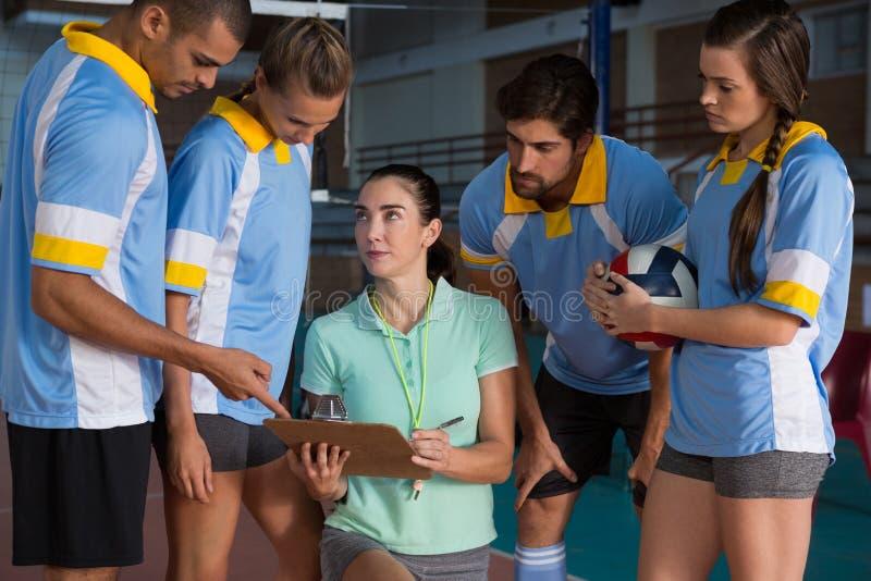 年轻女性教练谈话与排球运动员 免版税库存照片