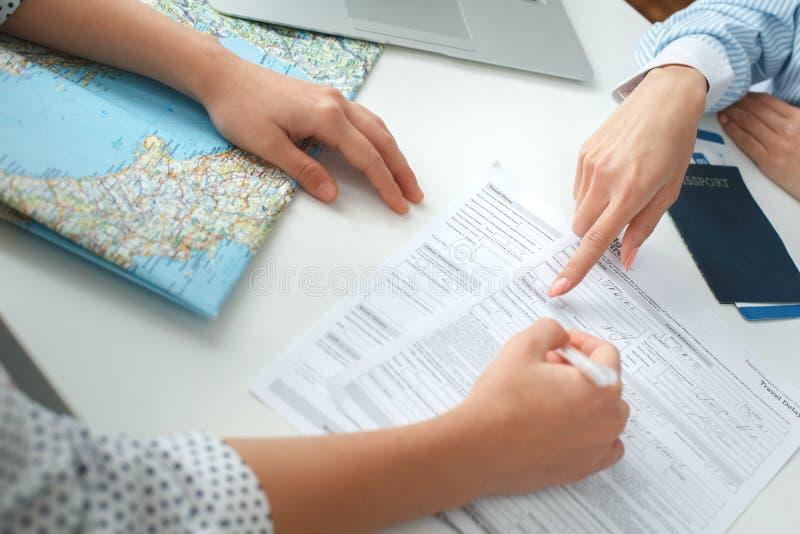 年轻女性旅行代理人顾问在与顾客签署的文件的游览机构中 库存照片