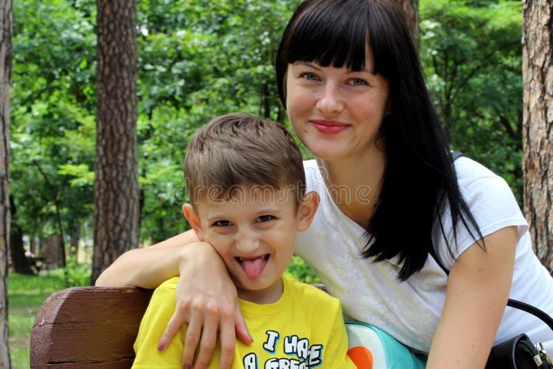年轻女性模型坐一条长凳在有她的小儿子的公园一件黄色T恤杉的 看照相机的儿子弯 免版税库存照片