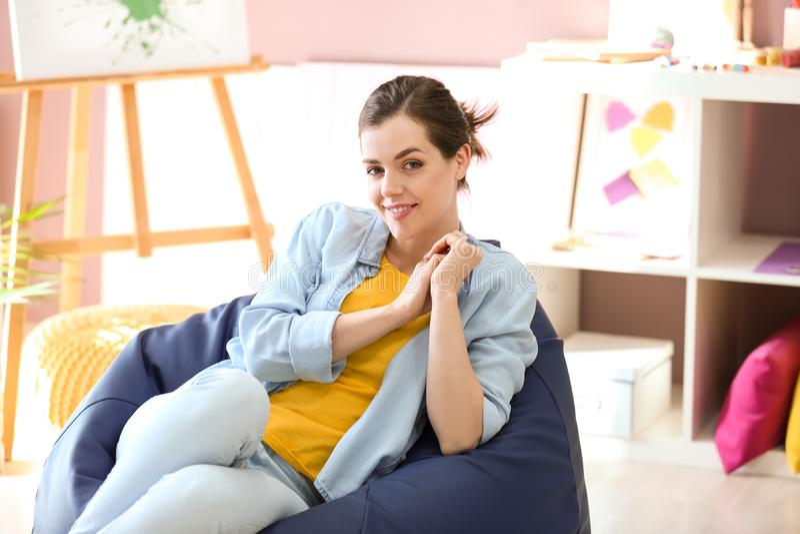 年轻女性画家坐装豆子小布袋椅子在演播室 免版税库存图片