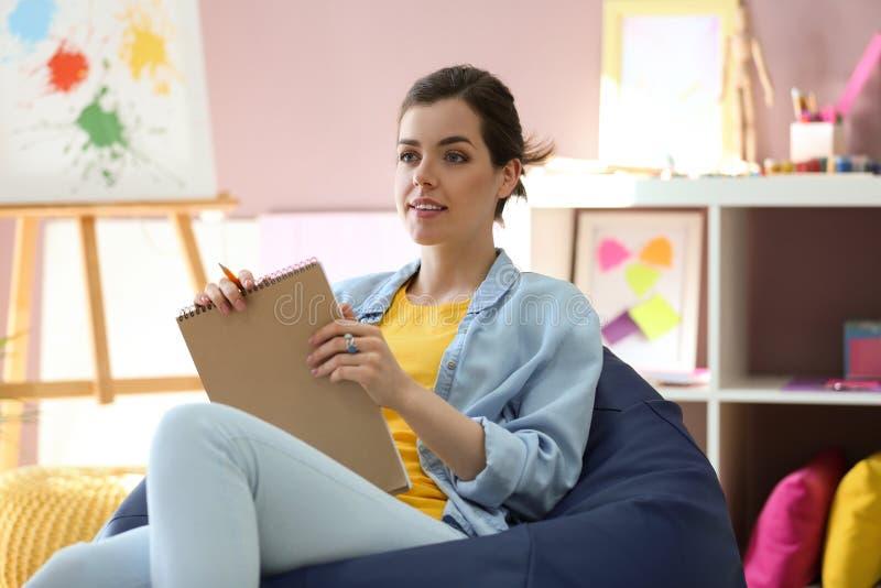 年轻女性画家坐装豆子小布袋椅子在演播室 库存图片