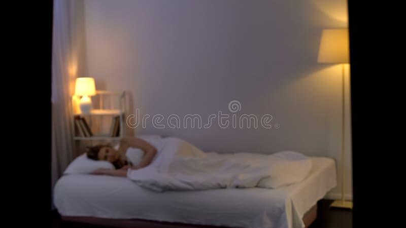 年轻女性睡觉在单独床上,夜休息,放松,健康生活方式 免版税库存照片