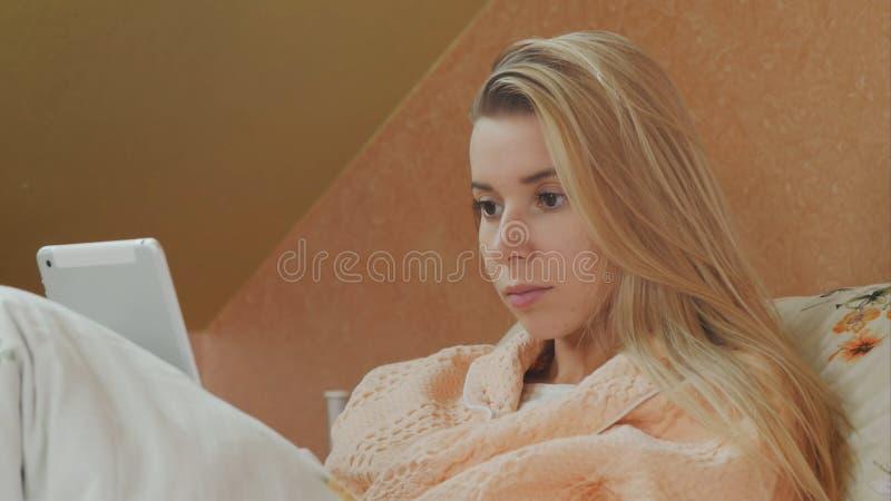年轻女性耐心用途数字式片剂在医院病床上 库存图片