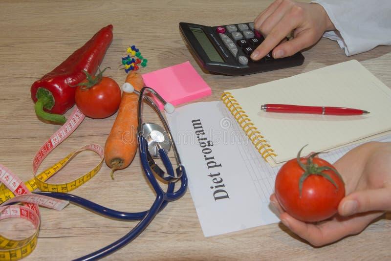 年轻女性营养师,工作在她的办公室的医生 免版税库存照片