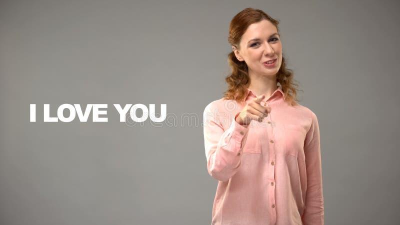 年轻女性说法爱您手语的,在背景的文本,打手势 库存图片