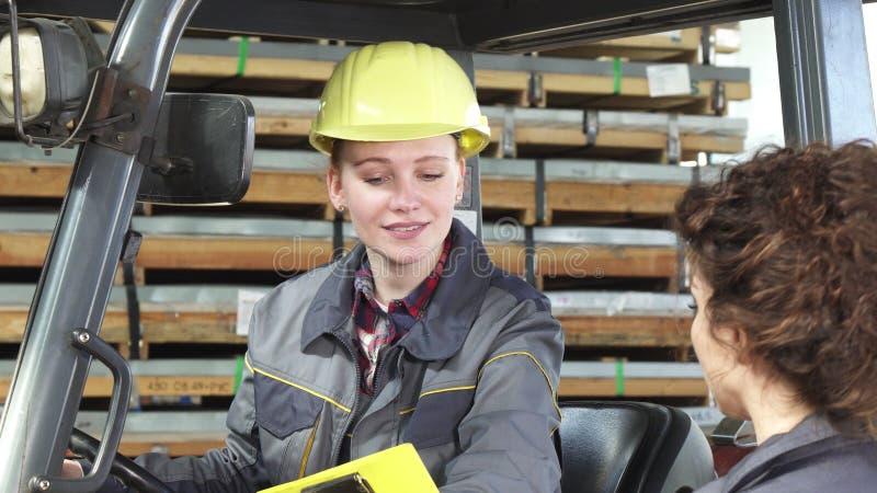 年轻女性fatory在存贮的工作者运行的铲车谈话与她的同事 库存照片