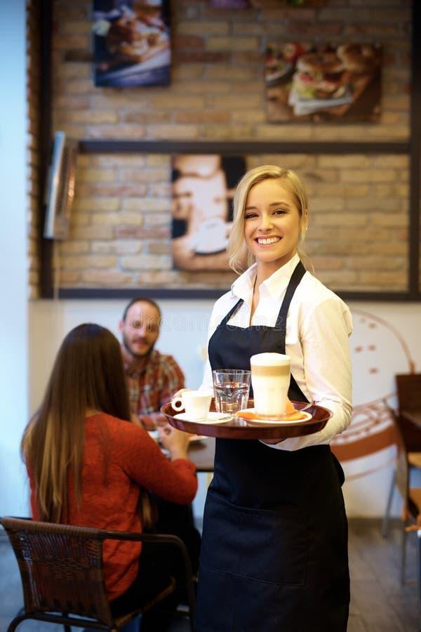 年轻女服务员微笑愉快 免版税图库摄影