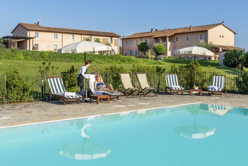 年轻女服务员服务游泳池边鸡尾酒给顾客坐在一种手段的一个懒人在比萨,意大利乡下  图库摄影