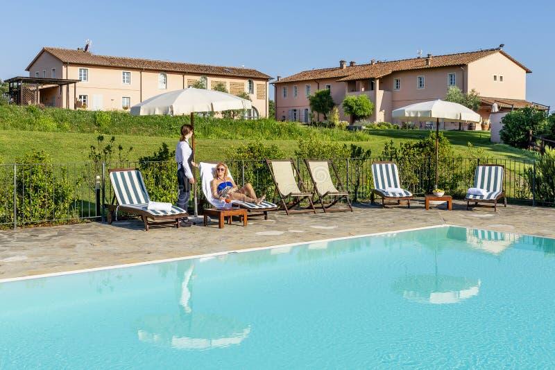 年轻女服务员服务游泳池边鸡尾酒给顾客坐在一种手段的一个懒人在比萨,意大利乡下  库存照片