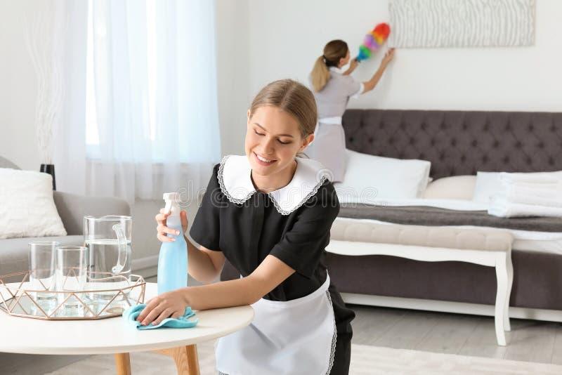 年轻女服务生清洁桌 图库摄影