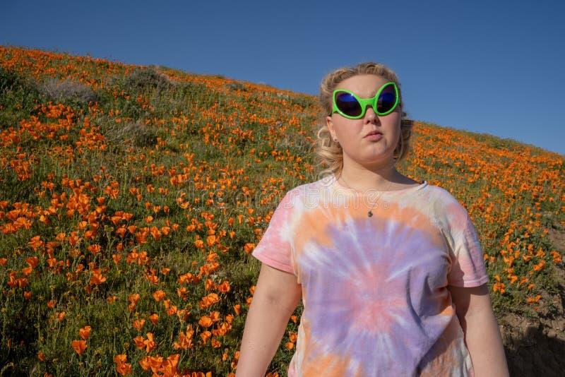 年轻妇女佩带的外籍人太阳镜和领带染料T恤杉在鸦片的领域站立 库存图片