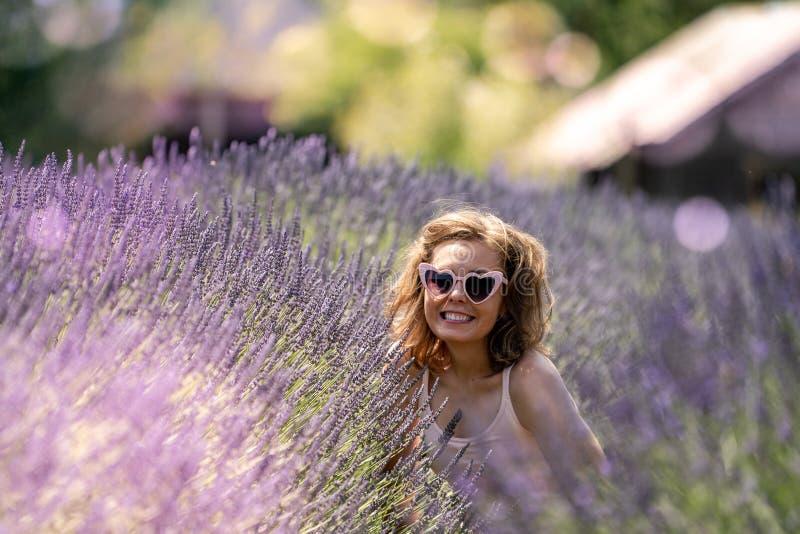年轻妇女佩带的心脏太阳镜在淡紫色的领域坐 免版税库存图片